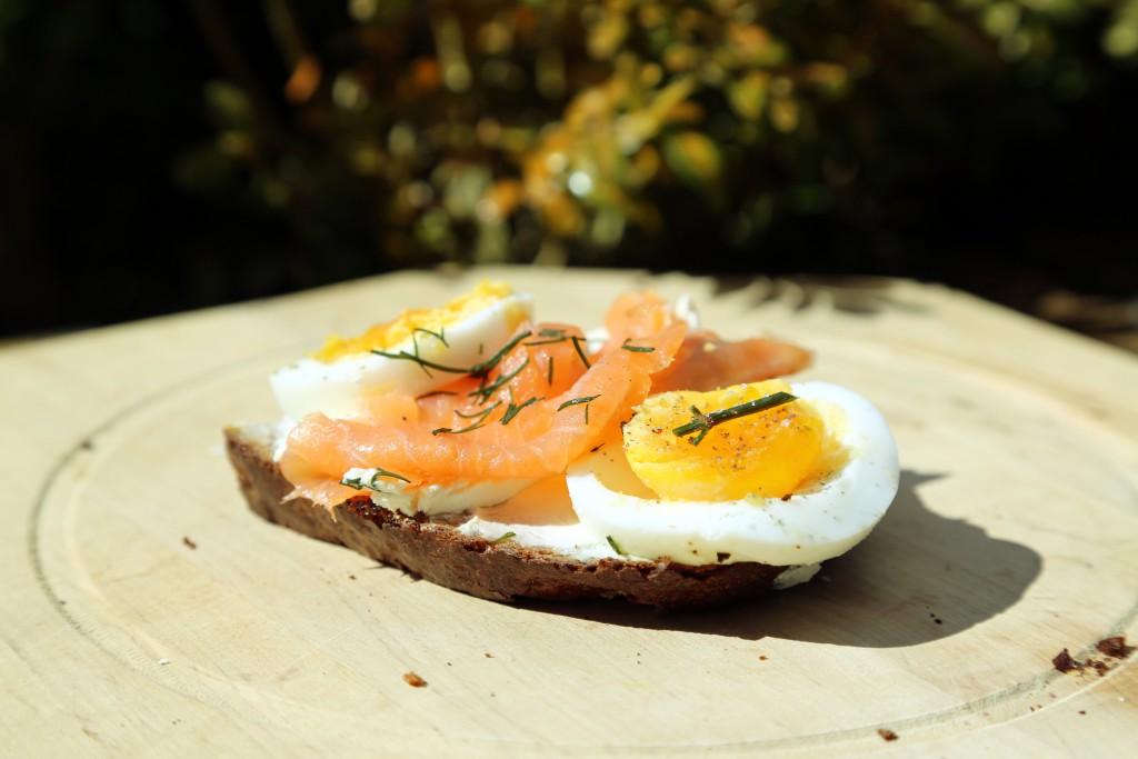 Chléb natřený lučinou, s uzeným lososem a vejcem.
