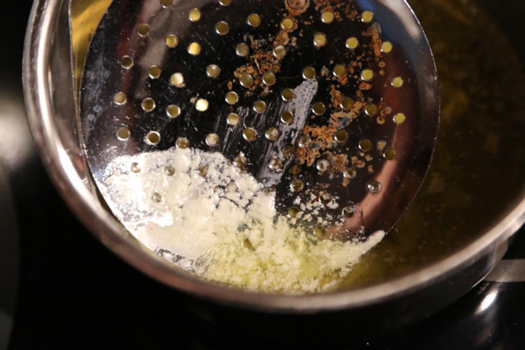 sbírání syrovátky z povrchu přepuštěného másla děrovanou naběračkou. Nechte probublávat na minimálním plameni a promíchávejte, aby se máslo nespálilo