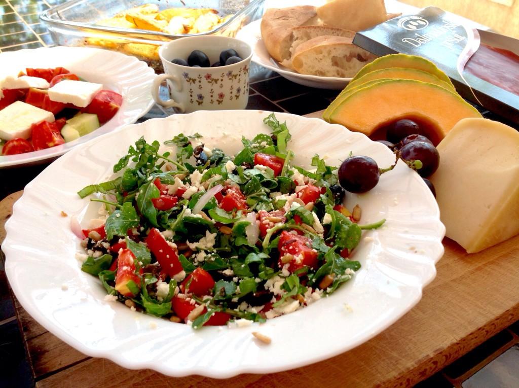 dalmatské polední menu v naší domácnosti: rukolový salátek, zralý sýr, sladké ovoce, místní nadýchaný chléb, samozřejmě pršut, olivy a brambory pečené s rozmarýnem