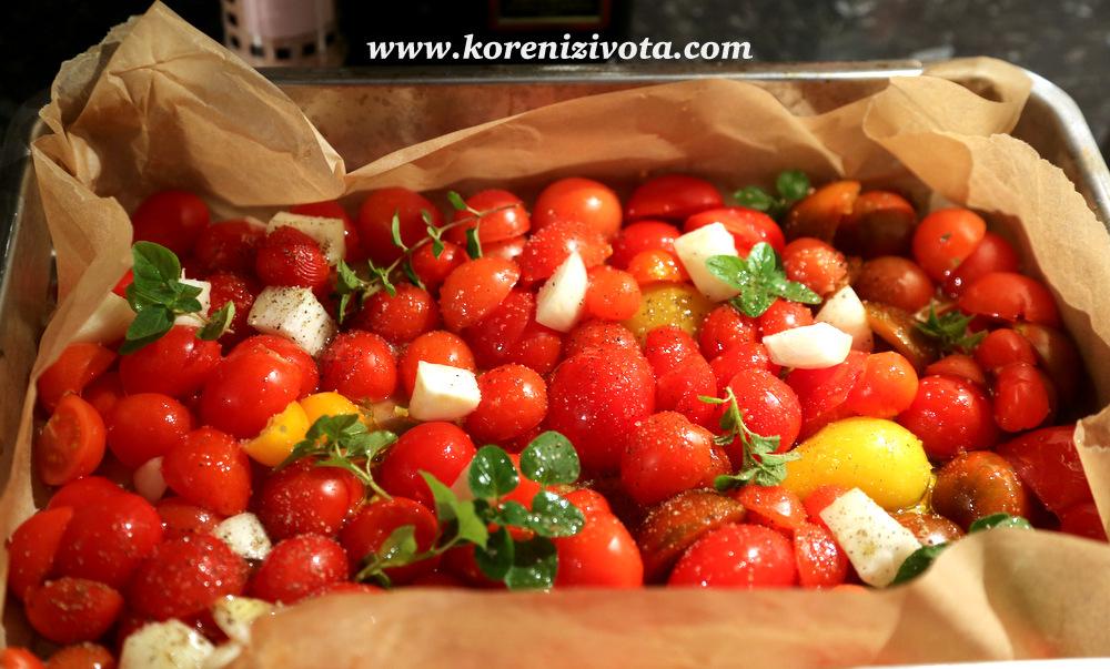 rajčata zbavte semínek, pokrájejte a řezem uložte na pekáč, přidejte cibuli, česnek, bylinky, osolte, opepřete a polijte olivovým olejem